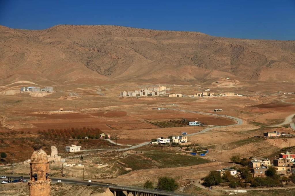 Arkada Raman Dağı'nın eteklerinde TOKİ evleri, sol önde minarenin üzerindeki leylek yuvası (Fotoğraf: Pınar Koyuncu)